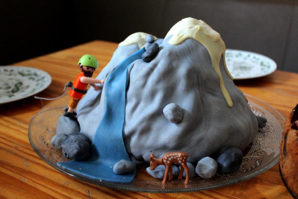 Torte als Berg und Bergsteiger dekoriert