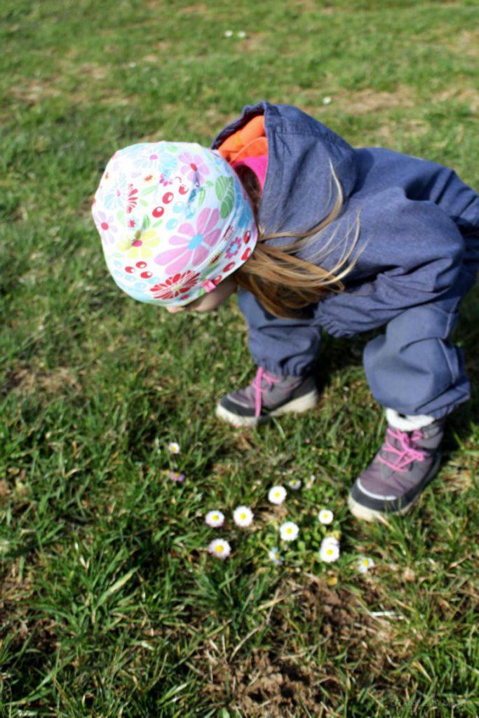 Kind und erste Gänseblümchen auf dem Feld