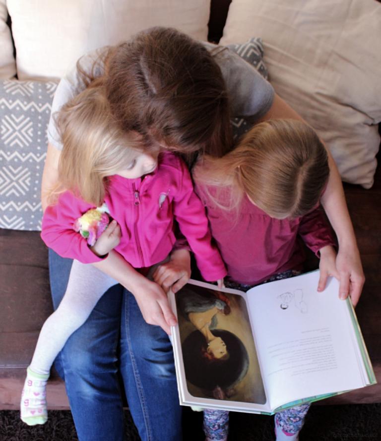 Mutter schaut mit ihren beiden Töchtern das Buch Mama von arsEdition an, zu sehen ist eine Illustration einer Frau mit großem Hut