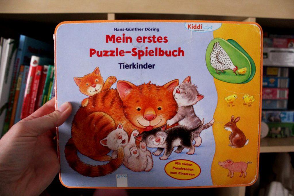 Kinderbuch Mein erstes Puzzel-Spielbuch vor einem Spielzeugschrank gehalten