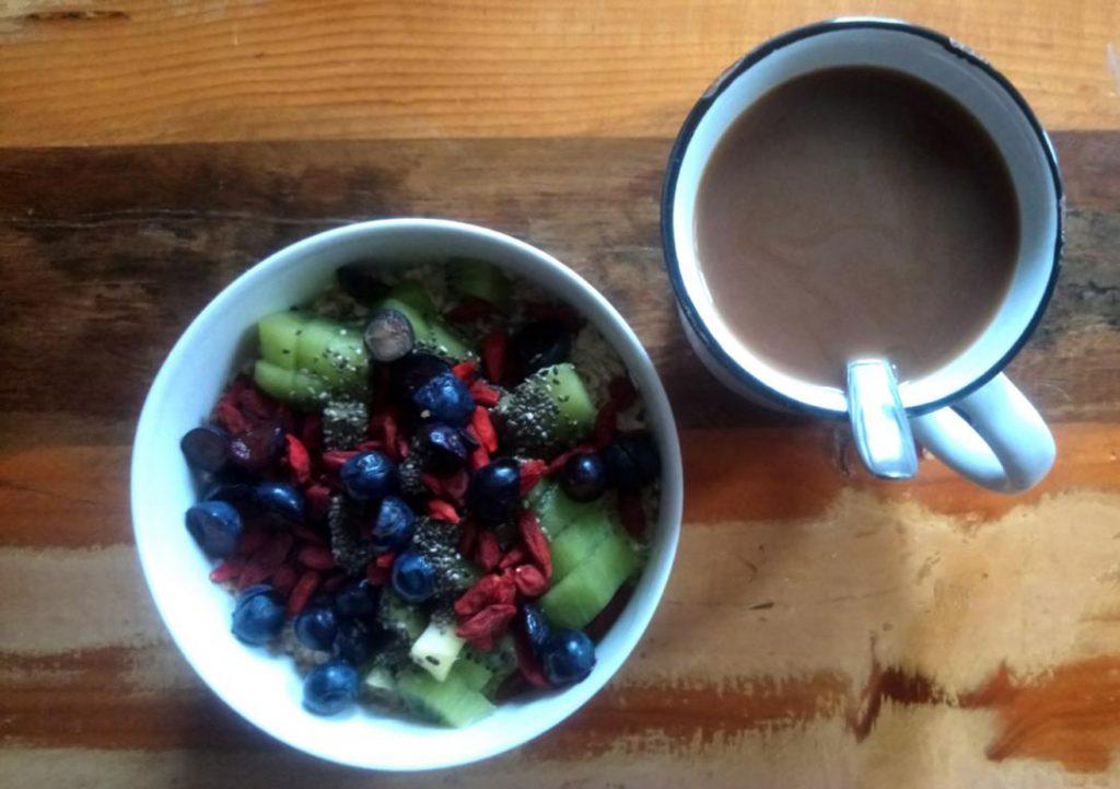 Frühstück mit Kaffe, Porridge und Obst