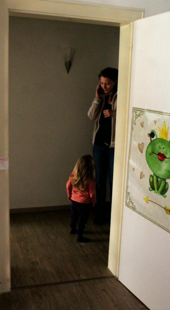 Mutter telefoniert und blickt dabei auf ihre Tochter