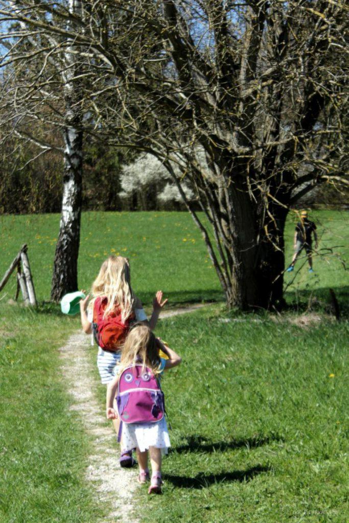 Zwei Mädchen laufen mit Osterkörben über die Wiese