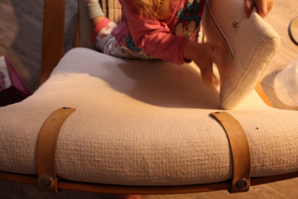 Kind macht Kopfkissen vom Poäng Sessel ab