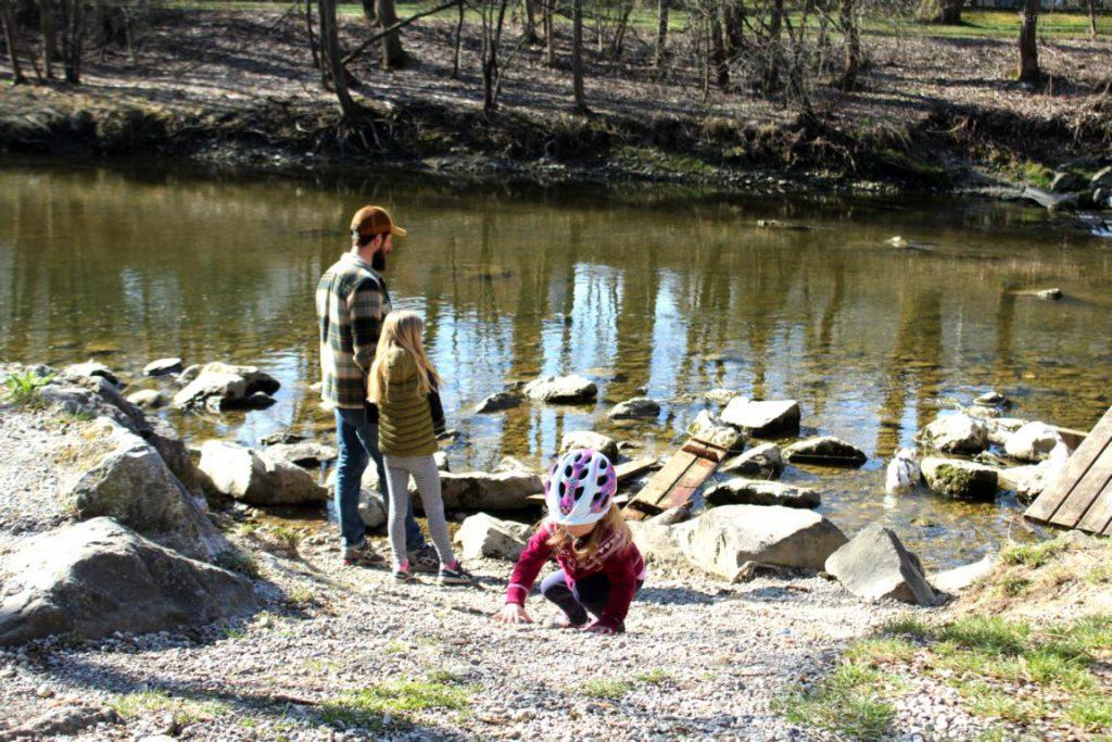Vater steht mit seinen zwei Töchtern am Fluss