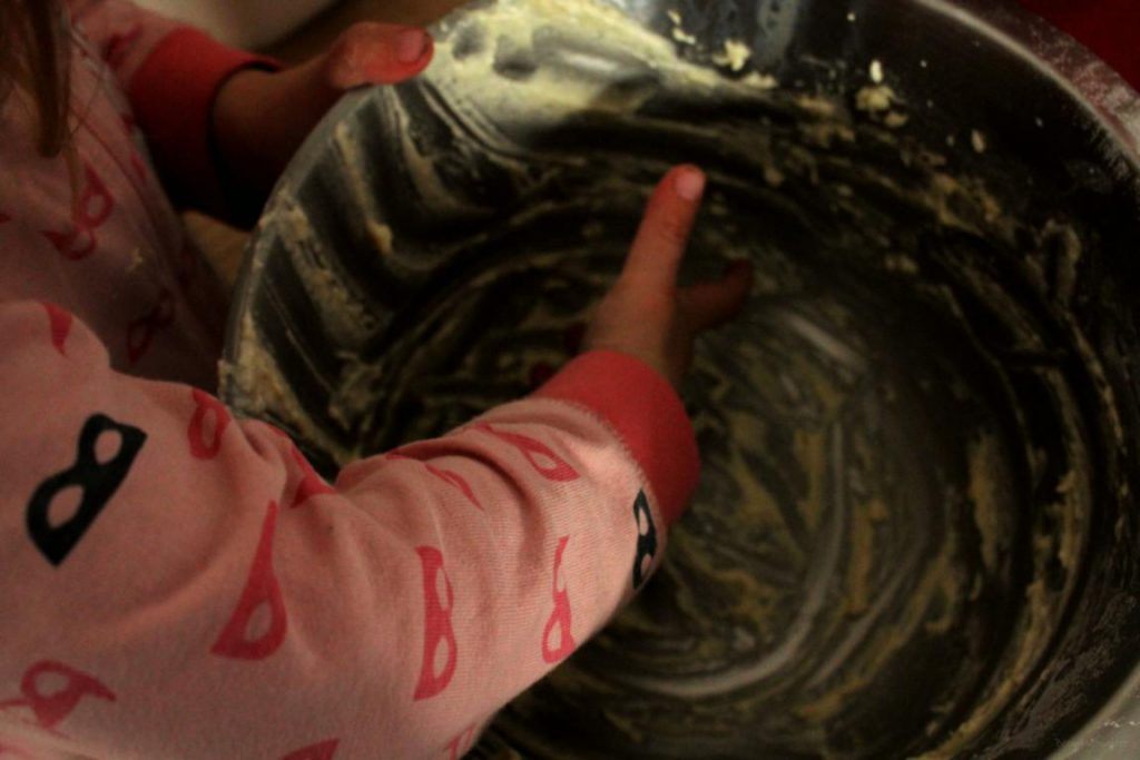 Kind nascht aus der leeren Teigschüssel