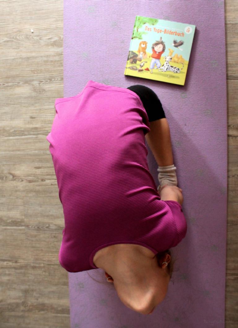 Kind macht Yoga, vor ihr liegt das Buch Das Yoga-Bilderbuch