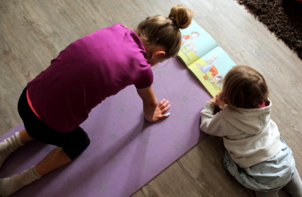 Kind macht die Yogaübung Katze auf einer Yogamatte