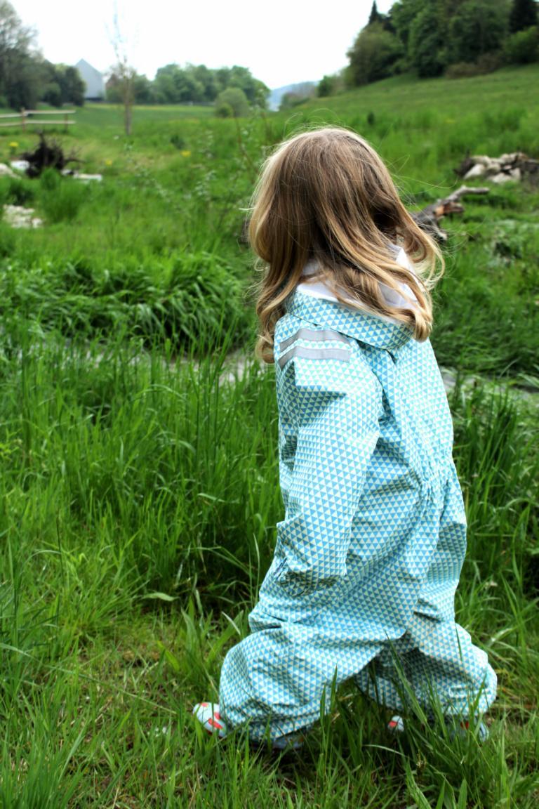 Mädchen steht auf einer Wiese am Bach