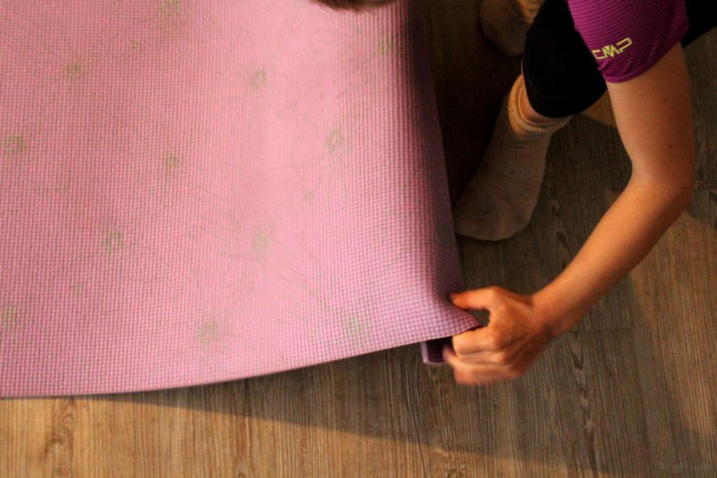 Jemand legt eine Yogamatte aus
