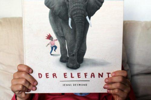 Kind hält der Buch Der Elefant von Jenni Desmond hoch