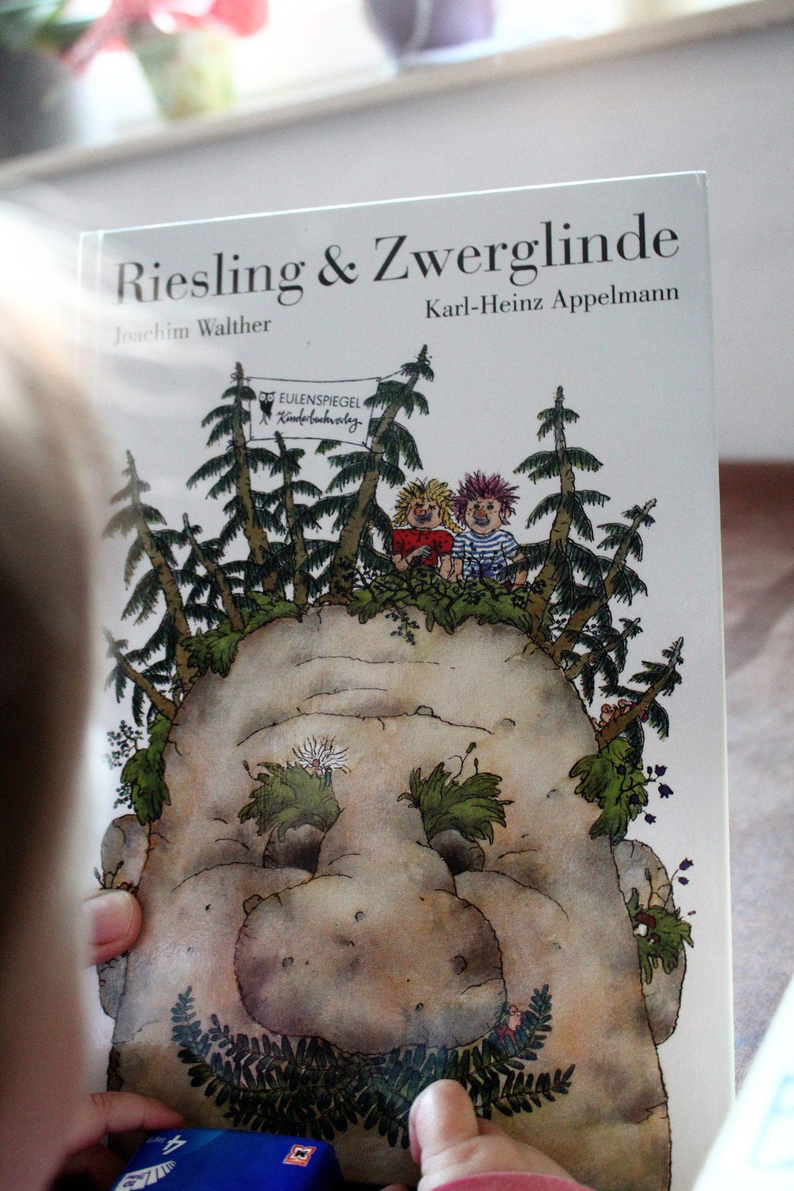Kind hält das Buch Riesling und Zwerglinde hoch