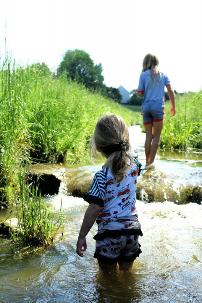 zwei Mädchen laufen durch einen Bach