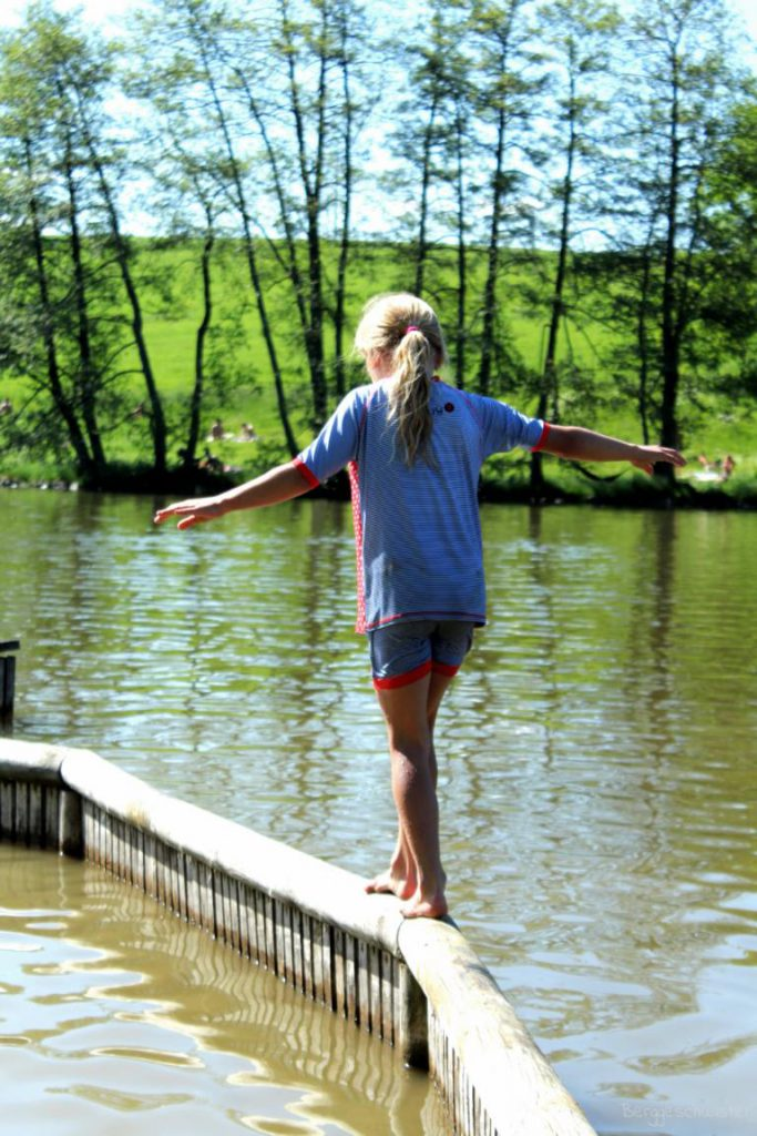 Mädchen balanciert auf einer Planke an einem See