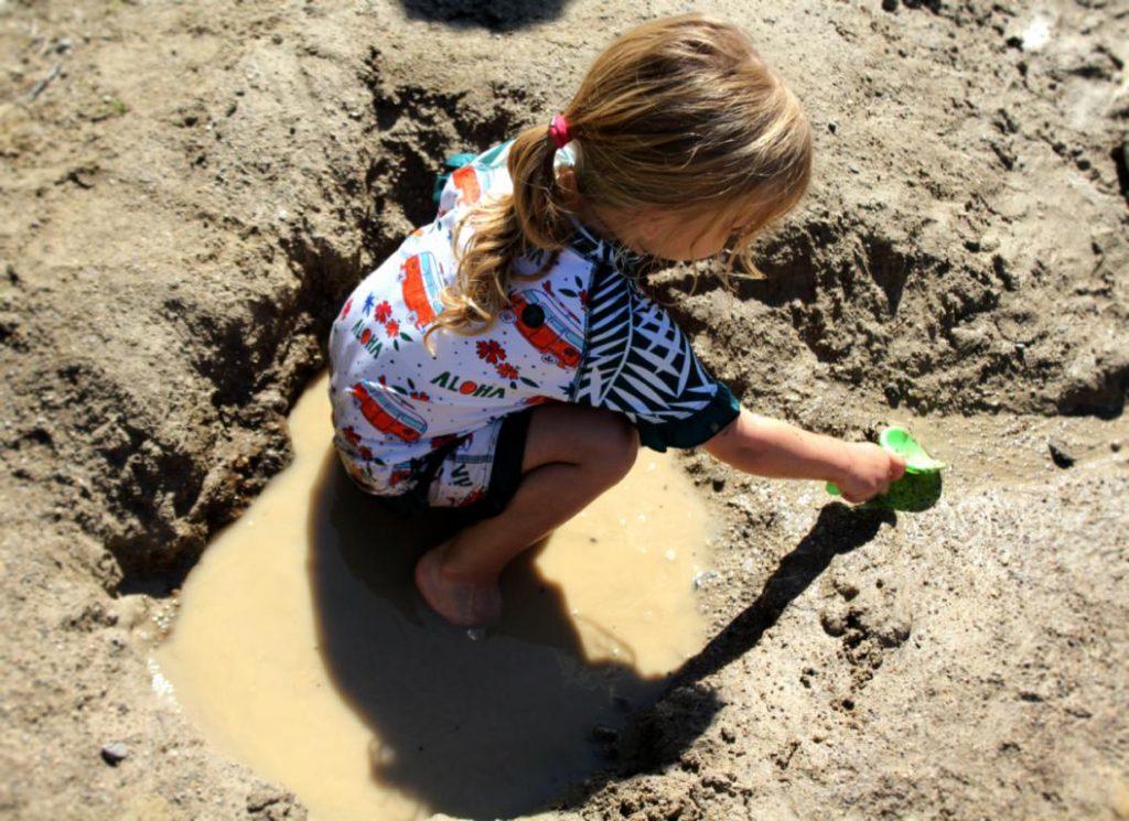 Kind spielt im Matsch am See