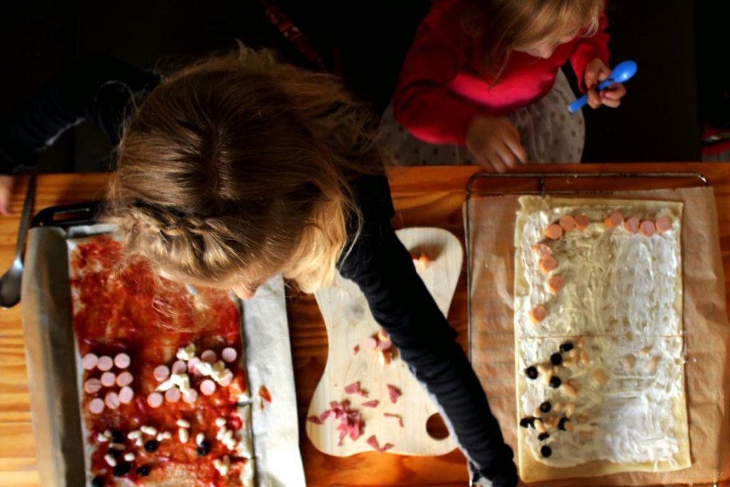 Zwei Mädchen belegen selber Pizza