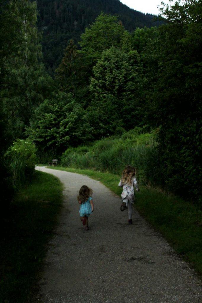 Mädchen rennen auf dem Rundweg am Weissensee bei Füssen