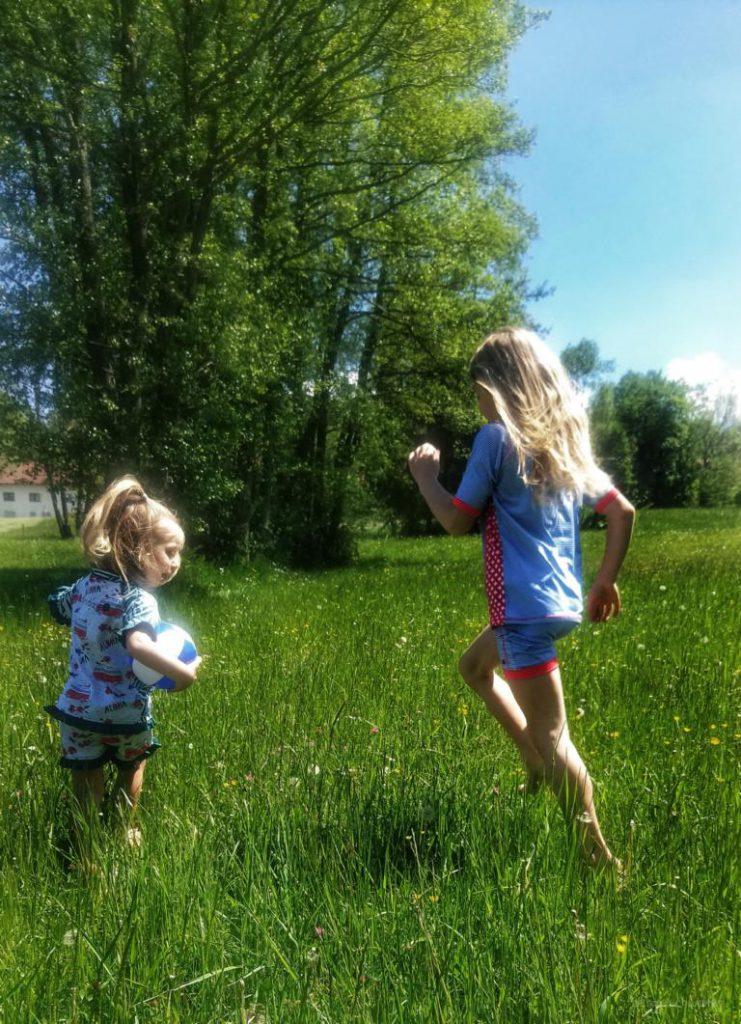 zwei Mädchenspielen auf einer Wiese