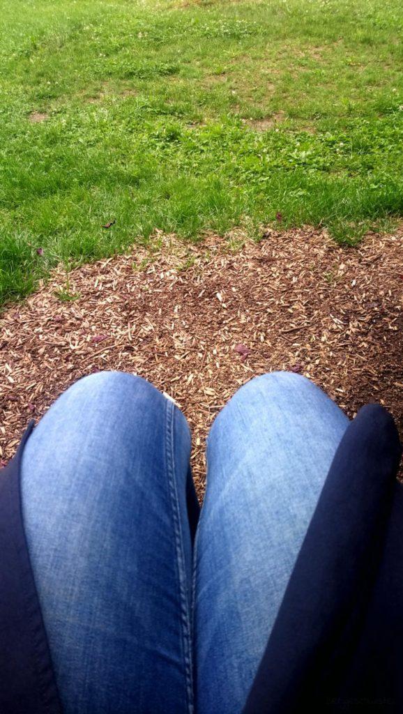 auf einer Bank auf dem Spielplatz sitzen