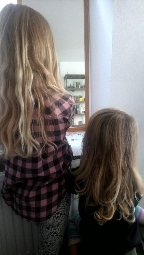 Zwei Mädchen von hinten vor einem Spiegel