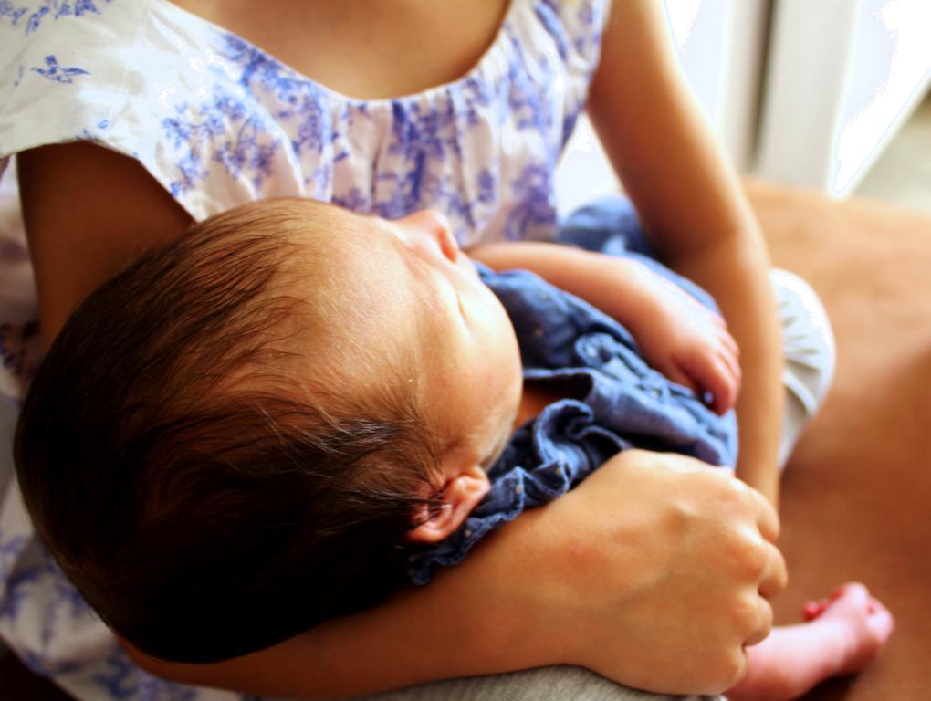 neugeborenes Baby im Arm seiner großen Schwester