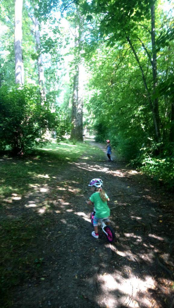 Mädchen fahren Laufrad und Roller