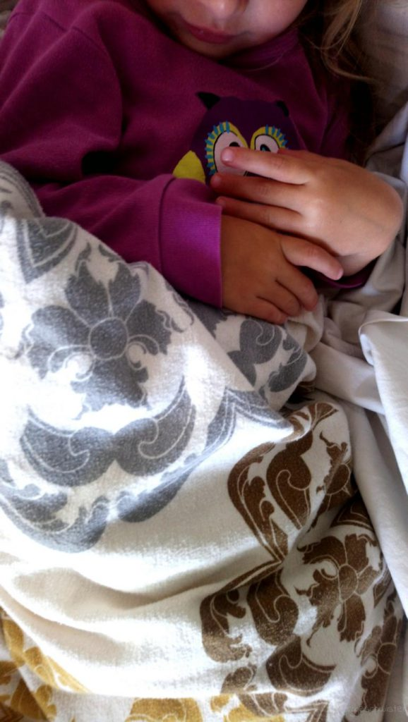 Mädchen liegt unter einer warmen Decke Bild für 12 von 12