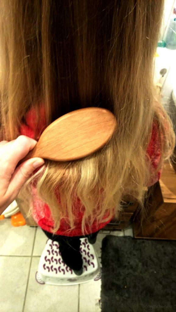 Mädchen werden die Haare gekämt