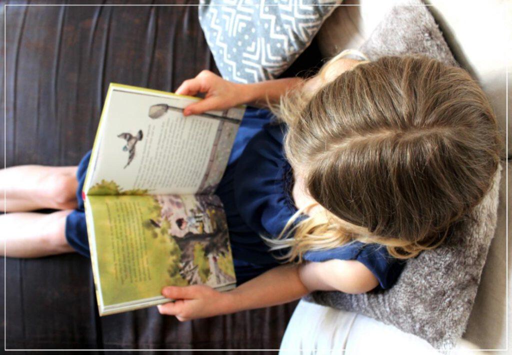Mädchen mit Buch auf dem Schoß