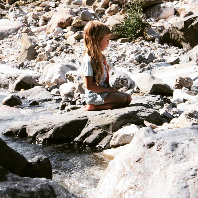 Mädchen auf einem Stein am Fluss