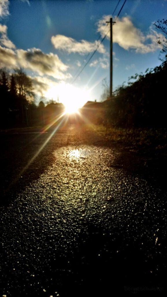 nasse Straße mit Sonnenschein