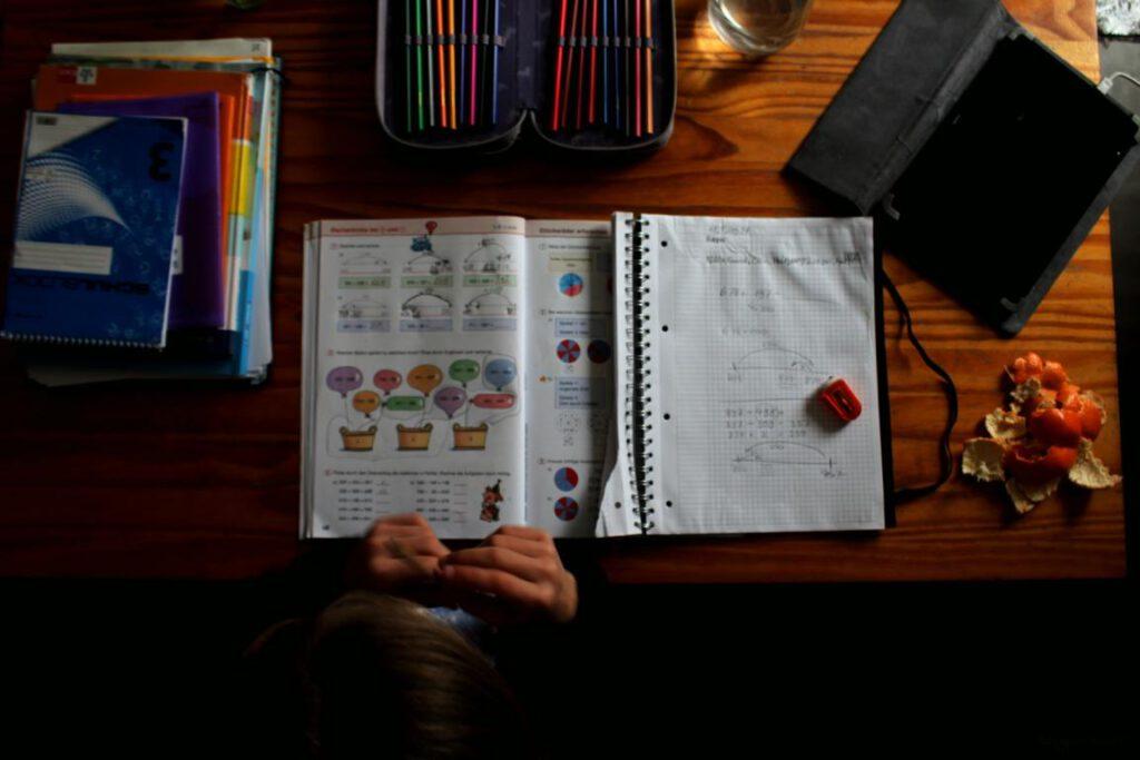 aufgeschlagenes heft und Mathebuch auf einem Tisch